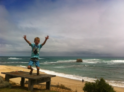 Young boy jumping for joy at Sorrento back beach