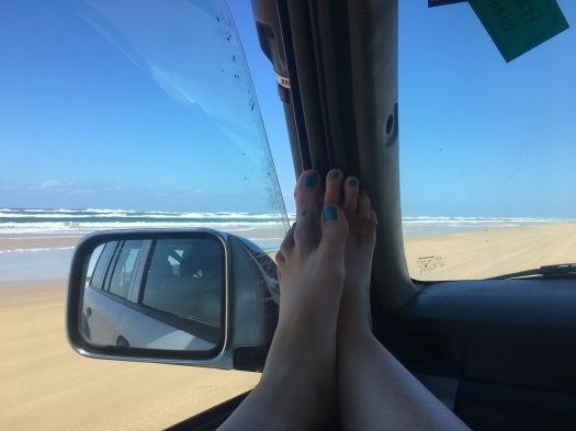 Feet on the dashboard while four wheel driving on the beach at Fraser Island